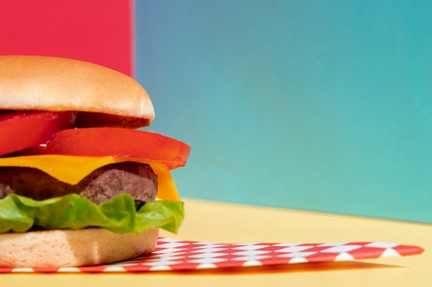 Arrangement with half cheeseburger on yellow table