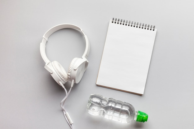 Arrangement with headphones, notebook and water bottle