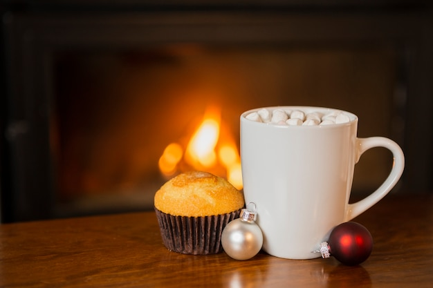 Arrangement with marshmallow drink and muffin near the fireplace