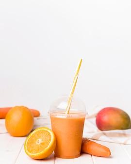 Arrangement with orange smoothie in cup
