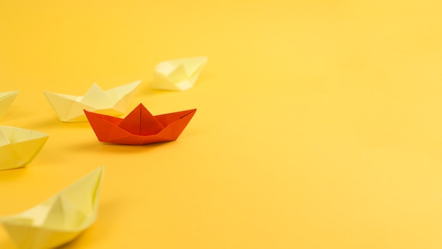 Arrangement with paper boats on yellow background and copy space