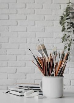 Disposizione con penne e pennelli in tazza
