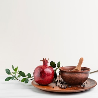 Arrangement with pomegranate and wooden bowl