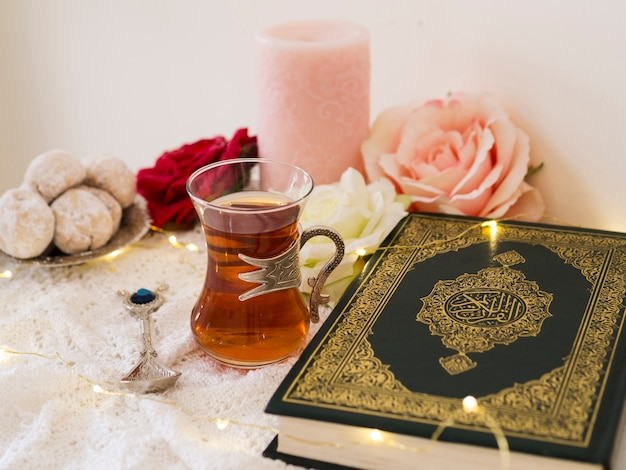 Arrangement with quran, roses, candles, tea and cookies