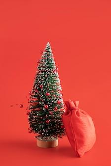 Disposizione con sacco rosso e albero