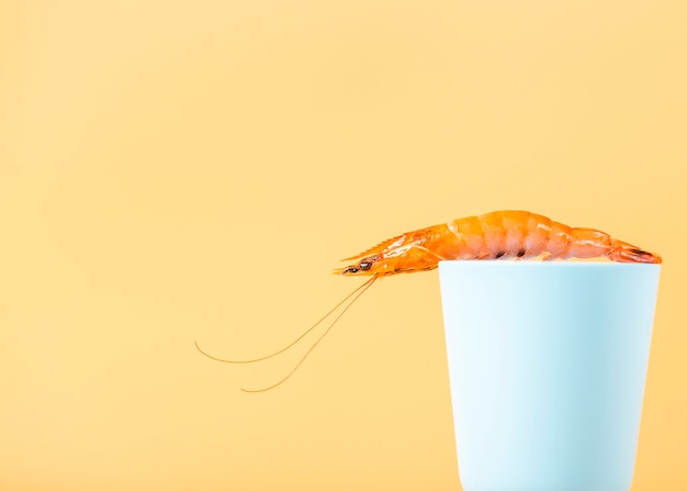 Arrangement with shrimp on cup with yellow background
