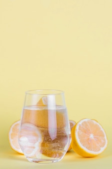 Arrangement with small glass of water and lemons