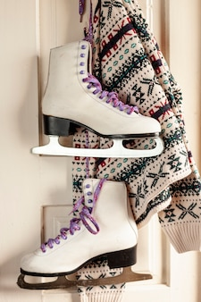 Arrangement with sweater and ice skates hanging
