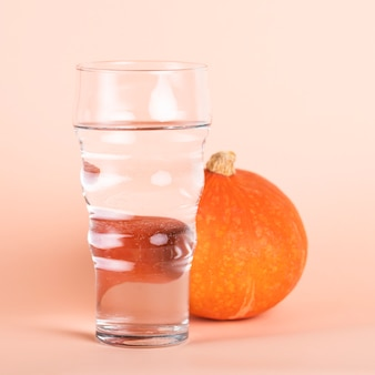 Arrangement with tall glass of water and pumpkin
