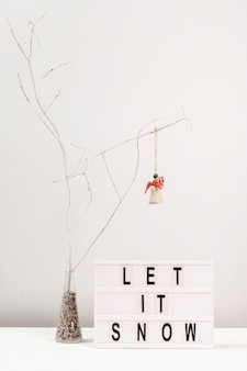 Arrangement with tree decoration and let it snow sign