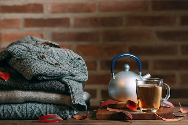 Arrangement with warm clothes and glass with tea
