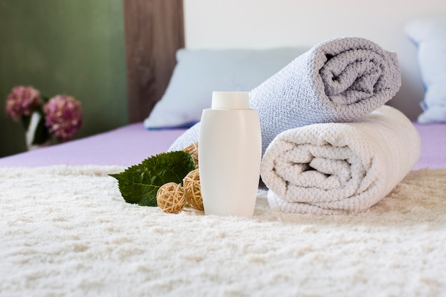 Arrangement with white bottle and towels on bed