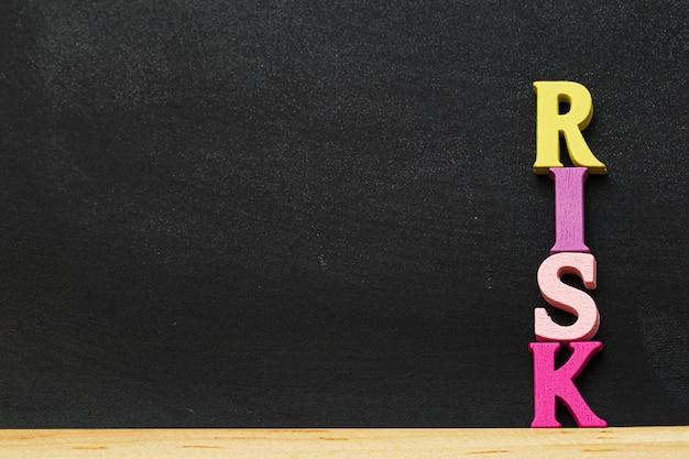 Arrangement wooden letters word risk on blackboard