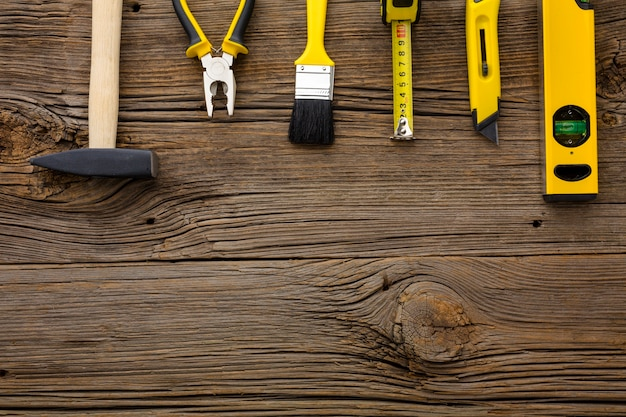 Arrangement of yellow repair tools on wooden background