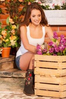 Аранжировка цветов со страстью. красивая молодая женщина устраивает цветы в горшке, сидя возле дома