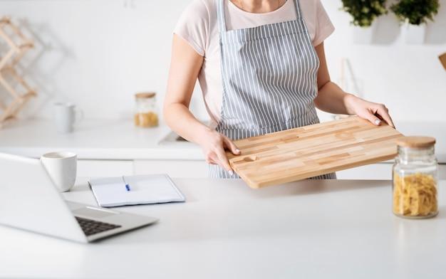 Расстановка посуды. элегантная осторожная симпатичная женщина кладет ингредиенты и разделочную доску на стол после того, как нашла и отметила рецепт пасты