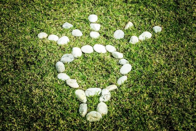 電球のエココンセプトで緑の草の上に白い石を並べる