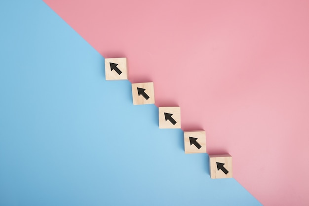 Arranging wood block stacking as step stair on pink and blue background, business concept growth success process. copy space.