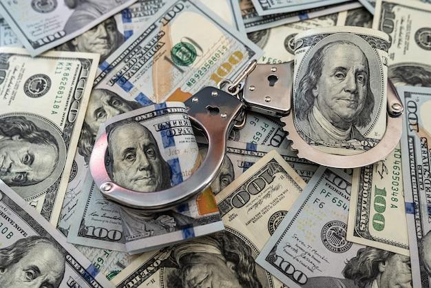 Арест преступников. металлические наручники на стодолларовые банкноты