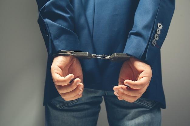 Арестованный мужчина с руками в наручниках сзади