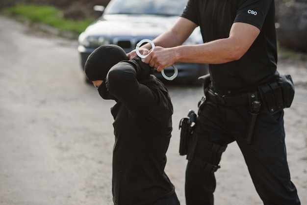 The arrested offender is kneeling and the policeman wears handcuffs on him. law and order.