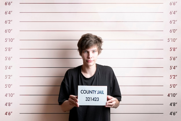The arrested prisoner young man holding a placecard in front of the height chart