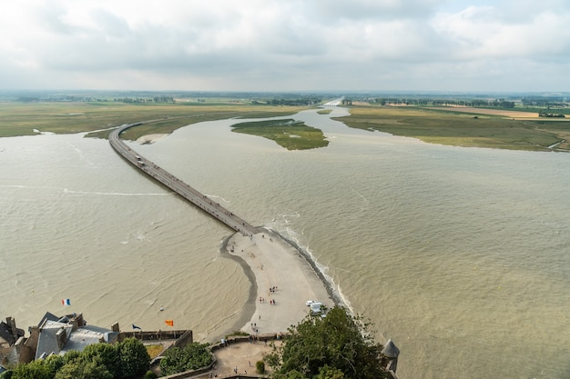 The arrival trail to the famous mont saint-michel abbey at high tide in the manche department, normandy region, france