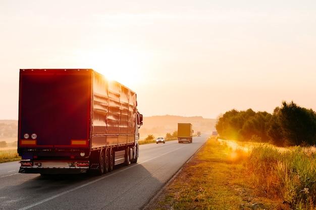 Прибывающий грузовик на дороге в сельском пейзаже на закате