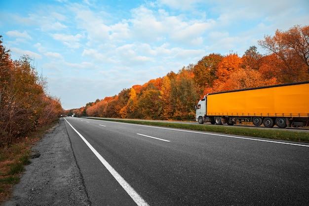 Прибытие белого грузовика на осеннюю дорогу
