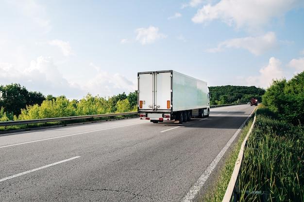 Прибытие белого грузовика на дороге в сельский пейзаж на закате