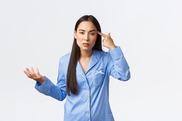 Arrogante ragazza asiatica che sembra frustrata e perplessa, indossa un pigiama blu, guarda con disprezzo mentre tocca tample e alza la mano confusa, rimproverando qualcuno che si comporta da stupido o pazzo