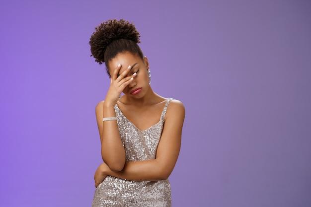 傲慢なイライラしたアフリカ系アメリカ人の女性は、退屈な顔の手のひらに手を閉じて唇をすぼめています...