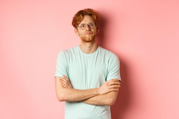 眼鏡をかけた傲慢な赤毛の男は、ピンクの背景の上に立って、懐疑的な顔で何かを見て、胸に腕を組んでいます。