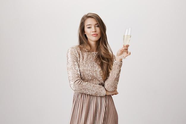 Высокомерная женщина в вечернем платье пьет шампанское