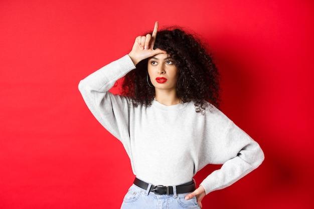 Высокомерная женщина с кудрявыми волосами, показывающая знак неудачника на лбу и смотрящая в сторону, издевающаяся над кем-то, стоящая на красной стене