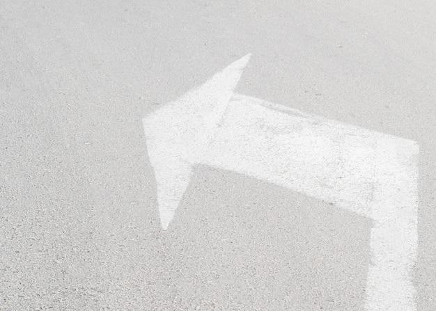 Arrow on asphalt pointing left
