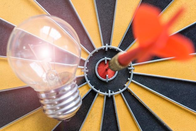 Arrow hitting the bullseye target with idea lamp on dartboard