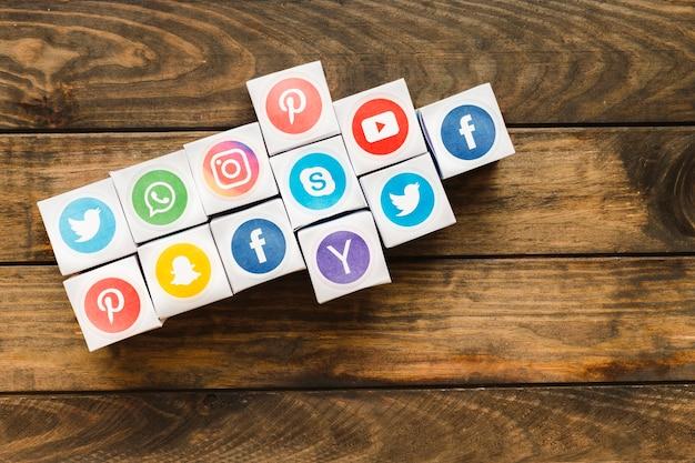 나무 판자 위에 생생한 소셜 미디어 아이콘 상자로 만든 화살표