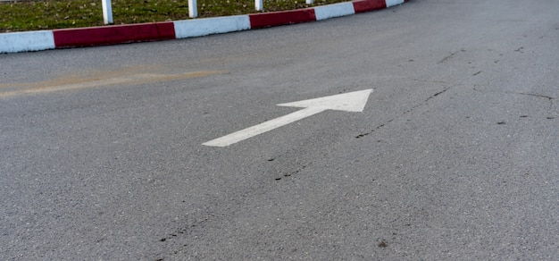 The arrow on the pavement showing the direction of movement of cars
