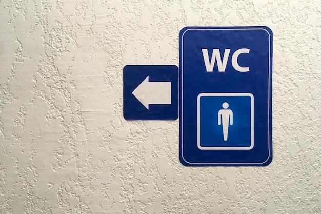 矢印、漆喰壁の公共男性トイレサインの青いプレート上のポインター。トイレのサイン。トイレのコンセプト.wc。水平ショット。スペースをコピーします。閉じる。屋内。