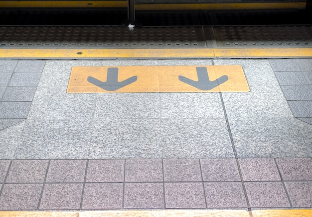 Arrow sign in flooring at train station, transportation sign