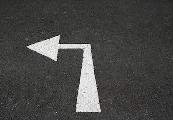 Arrow turn left marking sign on new asphalt road.