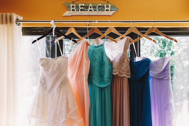 Arrow with lettering 'beach' hangs over the pastel dresses