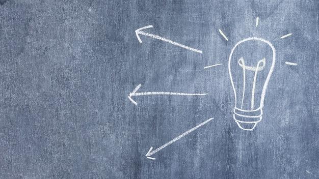 矢印と黒板にチョークで描か電球