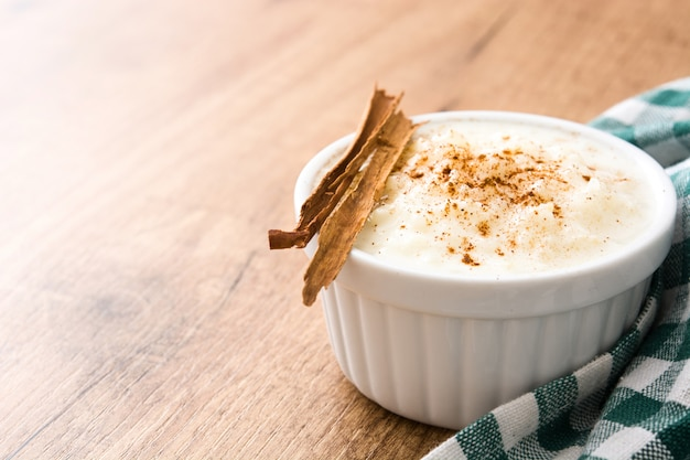 Arroz con leche or rice pudding with cinnamon on wooden table