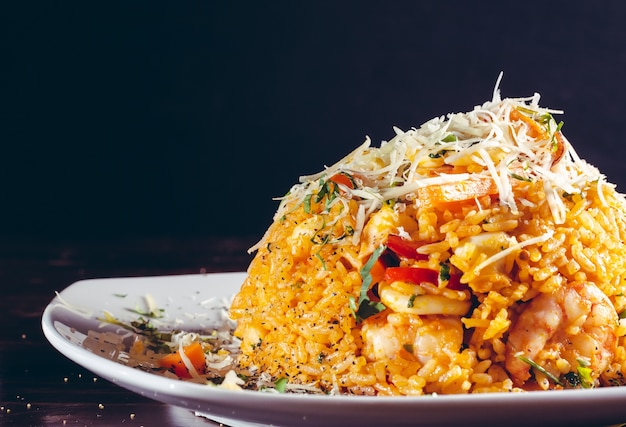 Arroz con mariscos rice whit seafood prawns typical peruvian food in wood table