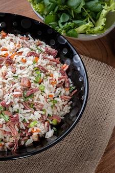 Аррос де карретейро - типичное блюдо южной бразилии, приготовленное из риса, сушеного мяса, колбасы пепперони, бекона и моркови. вид сверху