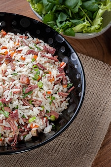 Arroz de carreteiro - typical food from southern brazil, made with rice, dried meat, pepperoni sausage, bacon and carrots. top view