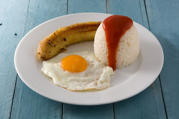 Arroz a la cubana typical cuban rice with fried banana and fried egg on a plate on wooden table.