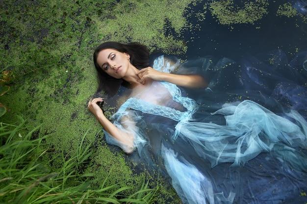 Искусство красивая романтическая женщина лежит в болоте в синем длинном платье с цветами. брюнетка портрета в прозрачном платье в ряске грязи болота воды. книжная обложка